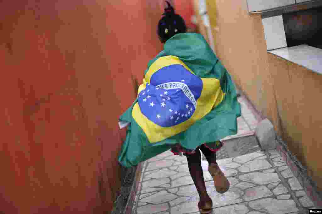A girl wearing the Brazilian flag runs through the slum of Varjao on the outskirts of Brasilia, ahead of the 2014 World Cup Group A soccer match between Brazil and Mexico, June 17, 2014.