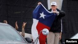 29일 홍수 피해를 입은 미국 텍사스주를 방문한 도널드 트럼프 대통령이 코퍼스크리스티시의 지역 소방소에서 피해 복구작업에 대한 설명을 들은 후 텍사스 주기를 들어보이고 있다.