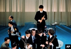 The Beatles are shown on stage with Ed Sullivan before their live television appearance on the The Ed Sullivan Show at CBS' Studio 50 in New York City, Feb. 9, 1964.