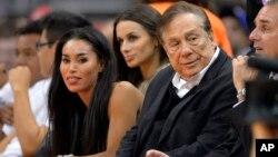Donald Sterling (derecha) y su novia V. Stiviano (izquierda) ven un juego de los Clippers en Los Ángeles.