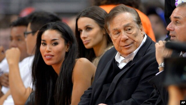FILE - Los Angeles Clippers owner Donald Sterling (R) and V. Stiviano (L) watch the Clippers play the Sacramento Kings during the first half of an NBA basketball game in Los Angeles.