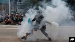 香港一名反送中抗议者把港警发射的一枚催泪弹抛回向港警。(2019年9月29日)