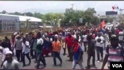 Para pengunjuk rasa berpawai melewati Kedutaan Besar AS di Port au Prince, Haiti, 29 Juli 2019. (VOA/S. Lemaire)