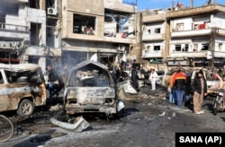 Syrian citizens gather at the scene where twin bombs exploded at a government-run security checkpoint in Homs province, Syria, Jan 26, 2016. State media said at least 22 people were killed and more than 100 others wounded.