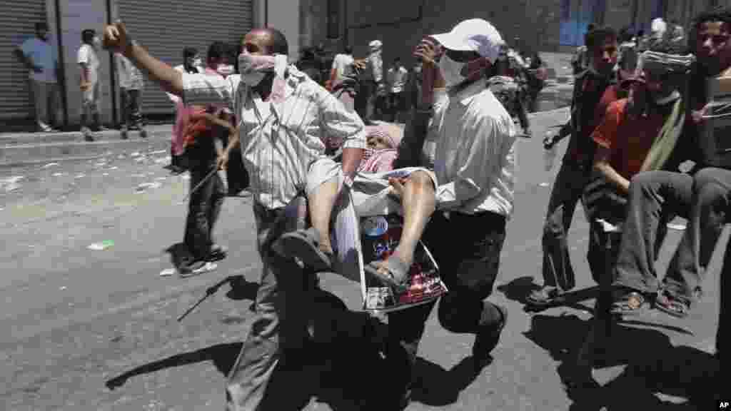 Des manifestants anti-gouvernementaux portent un homme blessé lors d'affrontements avec les forces yéménites à Taiz, au Yémen, 5 avril 2011.