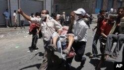 Des manifestants antigouvernementaux transportent un homme blessé lors d'affrontements avec les forces yéménites à Taiz, au Yémen, le 5 avril 2011. (AP Photo / Yemen Lens, File)