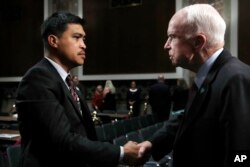 Senate Armed Services Committee Chairman John McCain, R-Ariz., right, shakes hands with Victor Sibayan, of Chula Vista, Calif., whose son, Navy Fire Controlman 2nd Class Carlos Sibayan, 23, died in the USS Fitzgerald collision, after a hearing on recent Navy incidents, Sept. 19, 2017, on Capitol Hill in Washington.