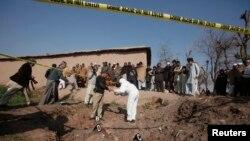 Thành viên đơn tháo dỡ bom mìn và cảnh sát Pakistan thu thập chứng cứ từ đống đổ nát của một ngôi nhà bị phá hủy sau vụ ném lựu đạn ở Peshawar, ngày 12/2/2014.