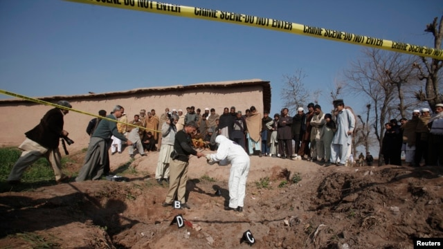 A member of bomb disposal unit and police collect evidence from the rubble of a house after it was destroyed with grenades thrown by gunmen on the outskirts of the northwestern city of Peshawar, Feb. 12, 2014.
