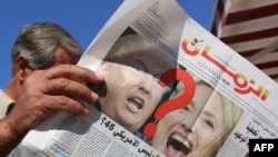 An Iraqi man holds an edition of Iraqi daily newspaper Azzaman displaying pictures of US presidential candidates Donald Trump and Hillary Clinton in Baghdad, Nov. 9, 2016.