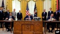 美國總統特朗普參加塞爾維亞總統武契奇(左)和科索沃總理霍蒂(右)在白宮橢圓形辦公室簽署關係正常化協議的儀式。(2020年9月4日)