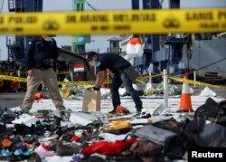 Para petugas forensik mengumpulkan sampel barang-barang dari pesawat Lion Air penerbangan JT610 yang jatuh di Laut Jawa. Barang-barang tersebut dikumpulkan di Tanjung Priok, Jakarta, 2 November 2018. (Foto:Reuters)