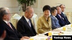 한국 박근혜 대통령이 13일 청와대에서 열린 국민원로들과의 오찬간담회에서 인사말을 건네며 자리에 앉고 있다.