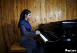 Negin Khpolwak, leader of the Zohra orchestra, an ensemble of 35 women, practices on a piano at Afghanistan's National Institute of Music, in Kabul, Afghanistan, April 9, 2016.