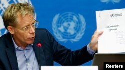 "World Health Organization Assistant Director General Bruce Aylward holds up a document titled ""Ebola response roadmap"" during a press briefing at the United Nations headquarters in Geneva, Aug. 28, 2014."