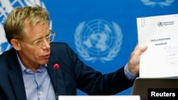 "World Health Organization (WHO) Assistant Director General Bruce Aylward holds up a document titled ""Ebola response roadmap"" during a press briefing at the United Nations headquarters in Geneva, Aug. 28, 2014."
