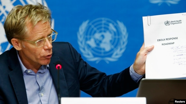 """World Health Organization Assistant Director General Bruce Aylward holds up a document titled """"Ebola response roadmap"""" during a press briefing at the United Nations headquarters in Geneva, Aug. 28, 2014."""