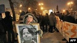 Một người cầm bức ảnh ký giả Baburova trong một buổi mít tinh tưởng niệm luật gia nhân quyền Markelov và ký giả Baburova
