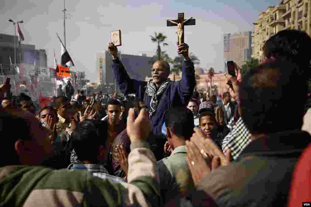타흐리르 광장에서 양손에 코란과 십자가를 들고있는 항의 시위를 벌이는 한 남자