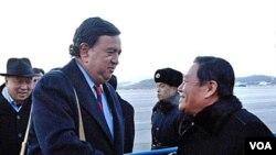 Pejabat Kementerian Luar Negeri Korut Li Gun menyambut Bill Richardson (kiri) di bandara Pyongyang, Korea Utara, Minggu, 19 Desember.