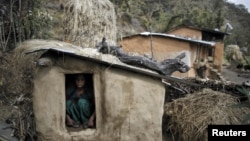 FILE - A woman sits inside a Chhaupadi shed in the hills of Legudsen village in western Nepal. Chhaupadi is the practice of treating women as impure and untouchable when they menstruate.