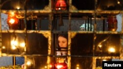 FILE - A woman places a candle during a commemoration ceremony at a monument for Holodomor victims in Kiev, Nov. 26, 2011.