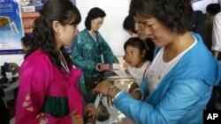 지난달 25일 평양에서 열린 무역박람회에서 시계 매대를 찾은 북한 주민들. (자료 사진)