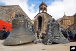 People look at bells, removed from the Dadivank, an Armenian Apostolic Church monastery dating to the ninth century, as ethnic Armenians leave the separatist region of Nagorno-Karabakh for Armenia, Nov. 14, 2020.