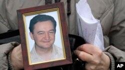 Bà Nataliya Magnitskaya cầm chân dung của con trai đã chết trong tù, luật sư Sergei Magnitsky, trong một cuộc phỏng vấn với AP.