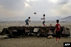FILE - Afghan boys play with a ball on top of the remains of a Russian armored vehicle in Kabul, Afghanistan, Oct. 6, 2011.
