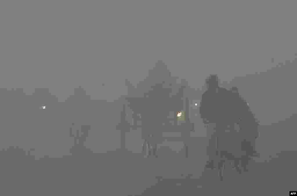 Pakistanlılar Lahor kentinde yoğun sis ve hava kirliliği altında seyahat ediyor. Pakistan'ın güneyinde hava kirliliğinin düzeyi kış mevsiminde artıyor ve Dünya Sağlık Örgütü standartlarının sık sık üzerine çıkıyor.