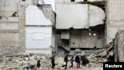 Halep'in el-Myassar mahallesinde bina enkazı içinde yürüyen çocuklar