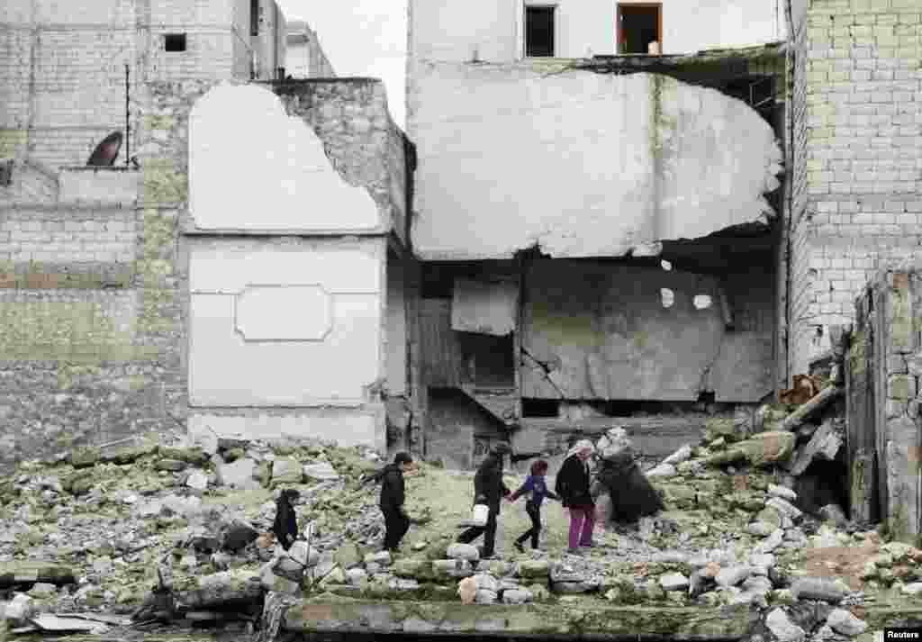 Trẻ em đi trên đống đổ nát của một tòa nhà bị hư hại trong khu phố al-Myassar của thành phố Aleppo, Syria.