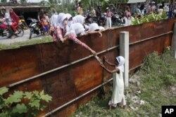 Học sinh Aceh đưa thực phẩm cho một bé gái Rohingya từ bên ngoài hàng rào của trại tị nạn tạm thời ở Bayeun, tỉnh Aceh.