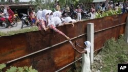 School children hand out food to a Rohingya young girl from outside the fence of a temporary shelter in Aceh province, Indonesia, May 21, 2015. (FILE PHOTO)