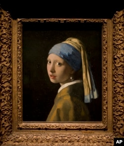 This reproduction shows Johannes Vermeer's Girl with a Pearl Earring (painted approximatetely 1665) at the renovated Mauritshuis museum during a preview for the press in The Hague, Netherlands, Friday, June 20, 2014.