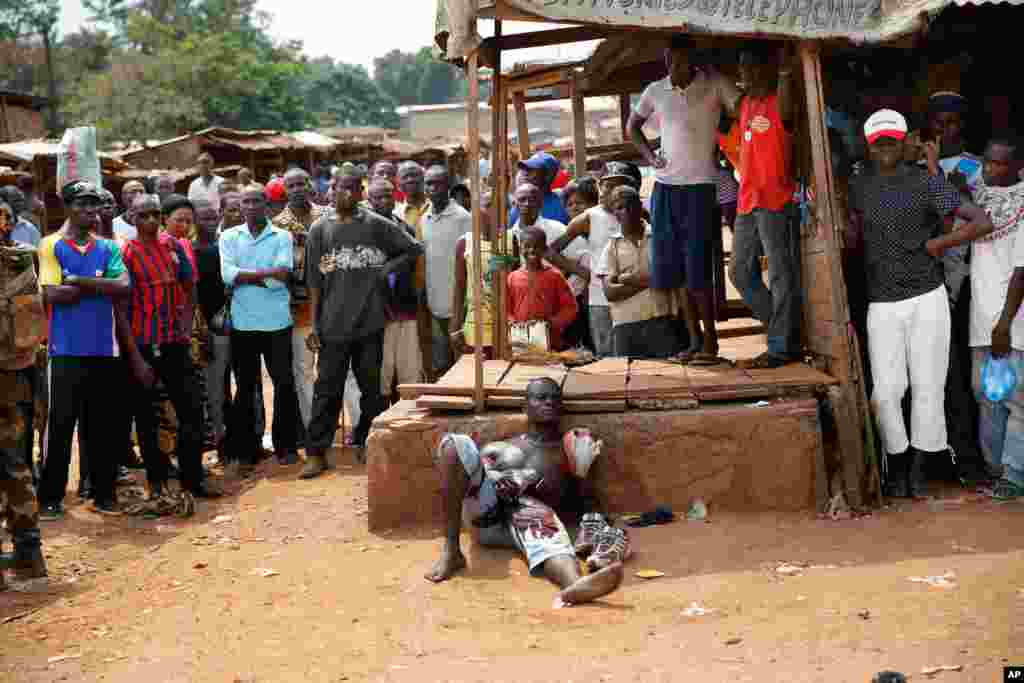 A suspected member of a militia lays wounded by machete blows in the Kokoro neighborhood of Bangui, Central African Republic, Dec. 9, 2013.