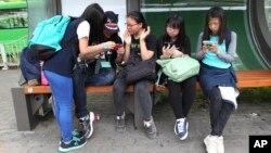 جنوبی کوریا کے ایک بس اسٹاپ پر طالبات سمارٹ فونز پر مصروف ہیں۔