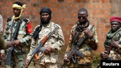 FILE - Seleka fighters warily eye a photographer at their base in Bambari, Central African Republic, on May 31, 2014.