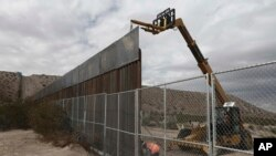 FILE - Workers raise a taller fence along the Mexico-US border between the towns of Anapra, Mexico and Sunland Park, New Mexico, Nov. 10, 2016. For almost two decades, a Mass has been celebrated there on the Day of the Dead to remember migrants who have died trying to cross the fence.