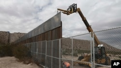 FILE - Workers raise a taller fence along the Mexico-US border between the towns of Anapra, Mexico and Sunland Park, New Mexico, Nov. 10, 2016. For almost two decades, a Mass has been celebrated there on the Day of the Dead to remember migrants who have
