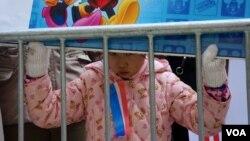 一位华裔小朋友手举卡通标语牌参加示威。(美国之音方方拍摄)