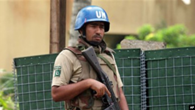 A UN soldier stands guard outside the Golf Hotel in Abidjan, 30 Dec 2010