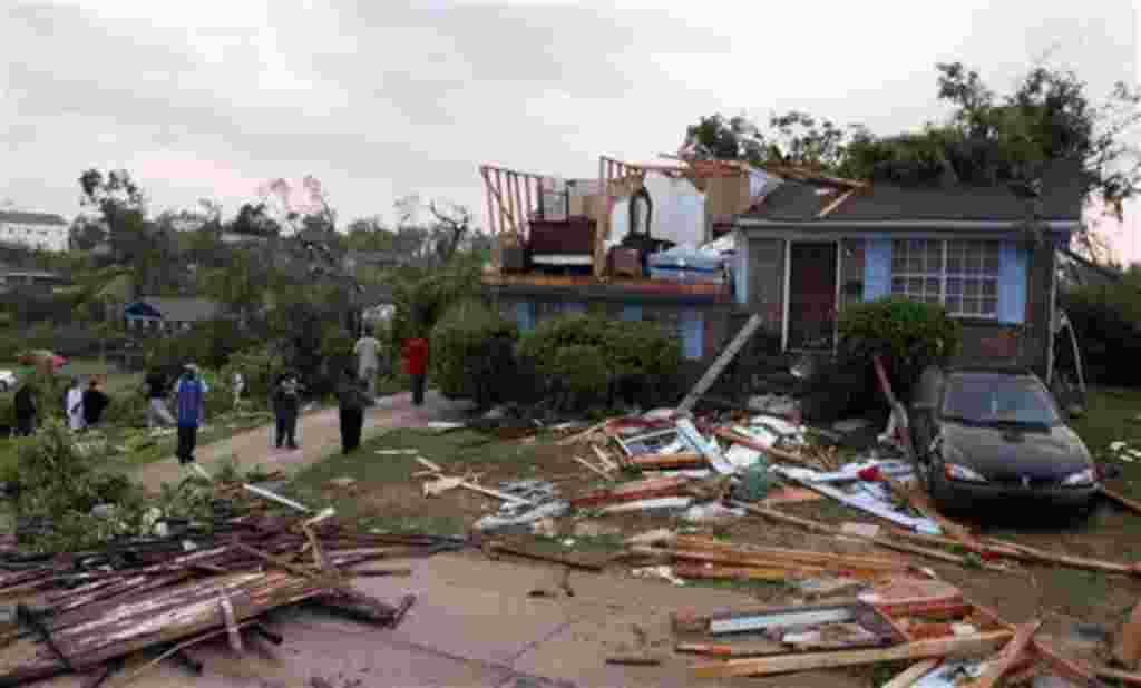 Los propietarios de las viviendas analizan los daños después del tornado en Pratt.