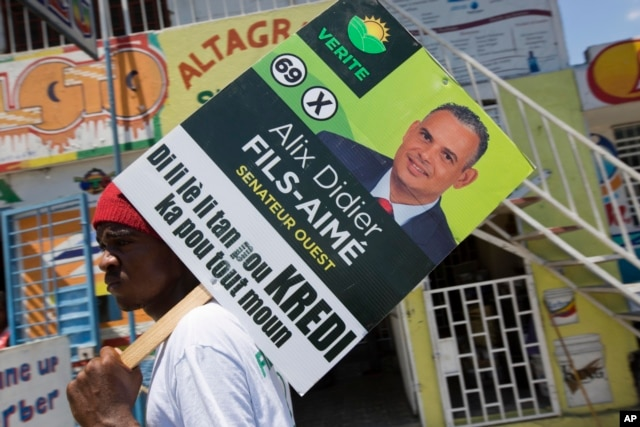 A supporter of the political party Platform Vérité carries a poster of parliamentary candidate Alix Didier Fils-Aime in Port-au-Prince, Haiti, Aug. 7, 2015.