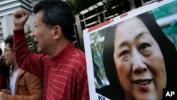 抗议人士在中国中央政府驻香港联络处外举行集会手举高瑜照片要求释放高瑜。著名媒体人高瑜曾经被电视认罪.(2015年11月27日)