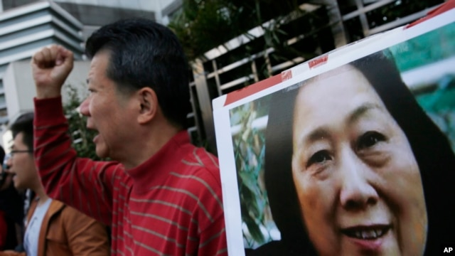 FILE - Anti-Beijing protesters hold a picture of veteran Chinese journalist Gao Yu during a rally outside the Chinese central government's liaison office in Hong Kong, as they demand the release of Gao, Nov. 27, 2015.