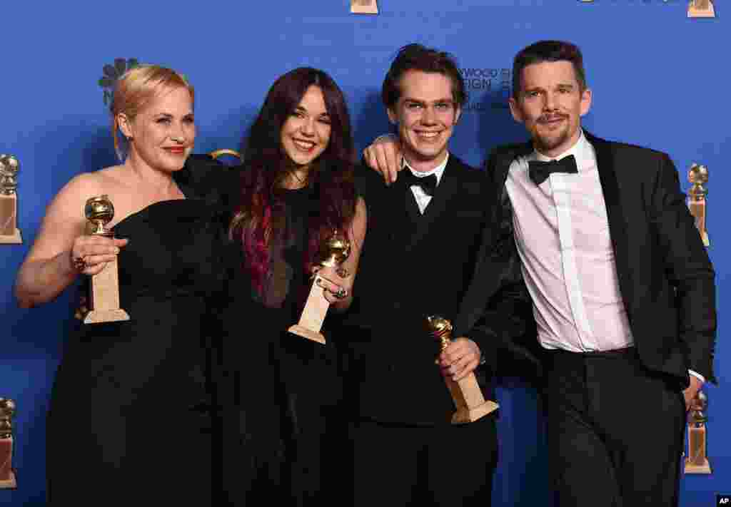 """Patricia Arquette, from left, Lorelei Linklater, Ellar Coltrane, and Ethan Hawke pose in the press room with the award for best motion picture - drama for """"Boyhood"""" at the 72nd annual Golden Globe Awards at the Beverly Hilton Hotel on Sunday, Jan. 11, 201"""
