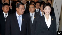 Cambodia's Prime Minister Hun Sen, left, walks with his Thai counterpart Yingluck Shinawatra as they attend ASEAN-UN Summit in Nusa Dua, Bali, Indonesia, Saturday, Nov. 19, 2011.
