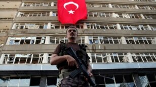 FILE - A Turkish special forces policeman stands guard in front of a damaged building inside the special forces policemen base, which was attacked during the failed military coup earlier this month, in Ankara, Turkey, July 19, 2016. Despite the chaos within the Turkish military, the PKK Kurdish rebel group has not launched any major attacks.